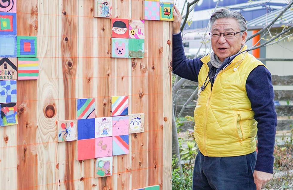 イトコー代表の伊藤正幸。イトコーマーケット20回記念のパネルの前で